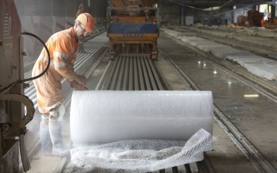 factory worker with bubble wrap roll on precast concrete beams